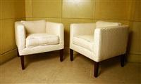 paire de fauteuils cubiques à dossier bas reposant sur des pieds en noyer by jean-michel frank