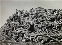 worker on top of pine log pile by margaret bourke-white