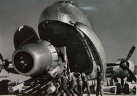 crewmen unloading huge b-50 bomber plane engine used as a spare from the belly of a c-124 cargo plane upon arrival at strategic air command's base, greenland, tx by margaret bourke-white