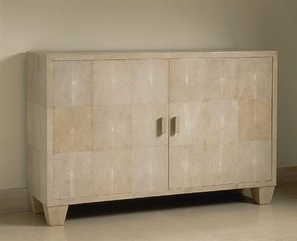 commode à deux portes entièrement recouverte de galuchat blanc ouvrant sur un intérieur en sycomore présentant trois tiroirs by jean-michel frank