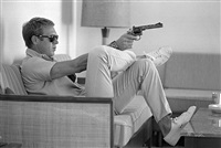 steve mcqueen aims a pistol in his living room, california, 1963 by john dominis