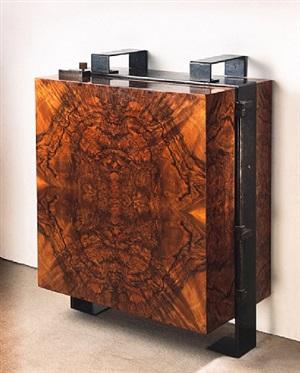 cabinet mural en placage de noyer et monture en fer battu patiné noir, ouvrant sur un intérieur en sycomore présentant des niches ouvertes et huit tiroirs by pierre chareau