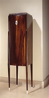 cabinet fuseau à une porte, en ébène de macassar. l'entrée de serrure et les sabots en ivoire by émile jacques ruhlmann