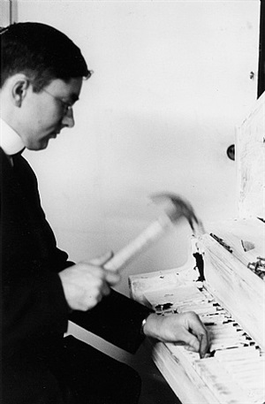 """george maciunas performing his """"piano piece no. 13"""" (aka """"carpenter's piano piece""""), fluxhall, 359 canal street, ny, may 9, 1964 by peter j. moore"""