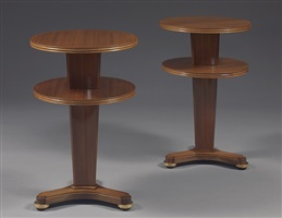 a pair of elegant american two-tire, circular walnut side tables supported on a curved, tripod leg, finished with gilt bronze feet by jules leleu