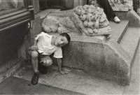 boy kneeling next to stone lion by helen levitt