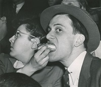 resourceful girl manages to watch man on the flying trapeze and feed hot dog to escort at same time by weegee