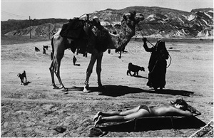 taba beach resort: a tourist sunbathing as a bedouin woman looks for clients for camel rides by micha bar-am