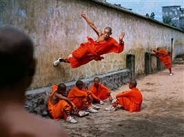 a young monk runs along the wall over his peers by steve mccurry