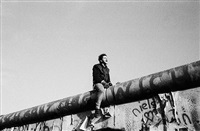 germany. berlin. november 11th, 1989. a young man bridges the wall between east and west berlin by raymond depardon