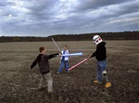 usa. wisconsin. 2007. raymond plays with star wars lightsabers with his sons brady and riley. by peter van agtmael