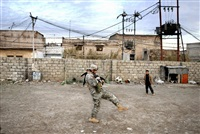 iraq. mosul. 2006. fully laden american soldier tries to play soccer with iraqi children. by peter van agtmael