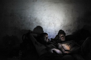 afghanistan. august 18, 2009. two marines watch a dvd before going to bed on fob sharp. the marine on the left had narrowly avoided being killed by an ied explosion earlier that day. by peter van agtmael