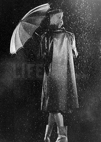fashion shot of model in raincoat holding umbrella by gjon mili