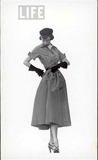 model dorian leigh wearing pin-point taffeta dress with full skirt by mollie parnis. long black gloves by gjon mili