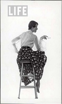model dorian leigh wearing white organdy shirt with full print skirt by ceil chapman (face seen in profile) by gjon mili